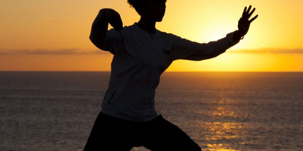 woman practicing Qi Gong at the beach