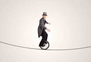 man riding unicycle on a rope