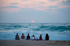 group meditating on beach
