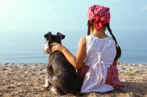 girl and a dog on a beach